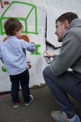 Young child using spray paint as part of Royal Mile mural